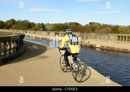 A cyclist on the Lancaster Canal tow path crosses The Lune Aqueduct in Lancaster UK - Stock Photo