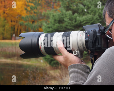 Nature photographer with large zoom lens - Stock Photo