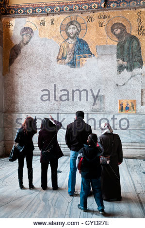 Tourists viewing the mosaic known as the Deesis Mosaic (The Last Judgement), depicting - left to right - Virgin - Stock Photo