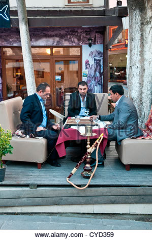 Three men relaxing at a cafe in the Old City of Istanbul, playing back gammon, Istanbul, Turkey. - Stock Photo
