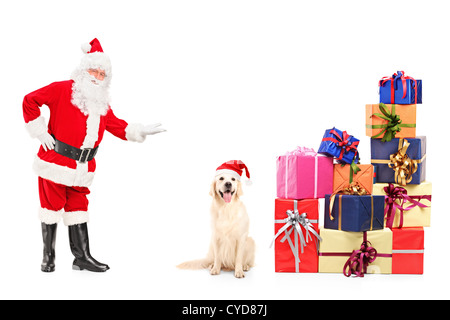 Full length portrait of Santa Claus and dog posing next to pile of gifts isolated on white background - Stock Photo