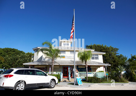 raising the american flag on a flagpole outside the chamber of commerce building in key largo florida keys usa - Stock Photo