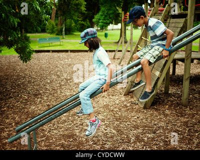 Brother and sister on slide made of two scaffold bars, New Zealand. - Stock Photo