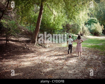Boy and girl walk along woodland path in afternoon sun - Stock Photo
