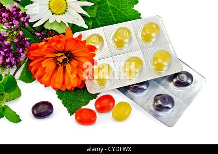 Lozenges cough multicolored, sprig of mint, sage leaf, chamomile, calendula, oregano isolated on white background - Stock Photo