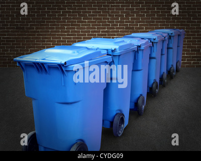 Recycle bins in a group made of commercial size blue plastic containers in a city street back alley against a brick - Stock Photo