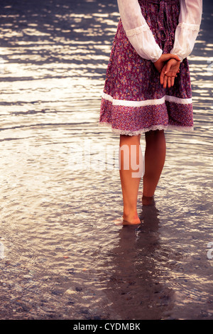 a girl in a vintage dress is standing in the water - Stock Photo