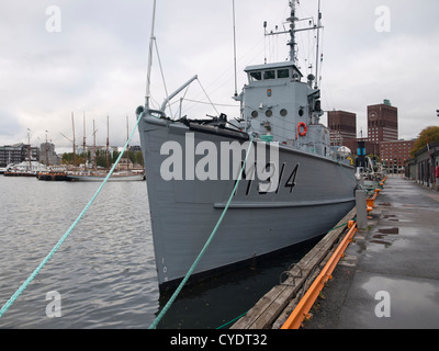 The Norwegian royal navy ship KNM Alta a minesweeper now museum ship moored in Oslo harbour with the Town Hall behind - Stock Photo