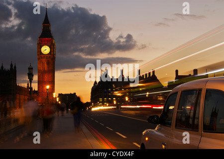 As the world passes by a taxi cab stops on Westminster Bridge next to the Houses of Parliament in London - Stock Photo