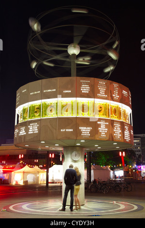 Couple under World clock or Weltzeituhr in Berlin at night - Stock Photo