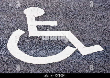 Disabled person sign painted on tarmac to show area of disabled parking - Stock Photo