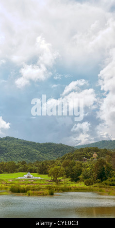 A large golden buddha sits on a hillside overlooking the area of Hua Hin in Thailand. - Stock Photo