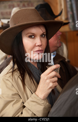A tough western woman looks at the camera before drinking her alcohol. - Stock Photo