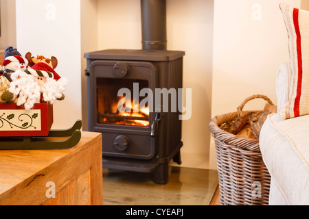 Wood burning stove and christmas ornaments in a modern living room - Stock Photo