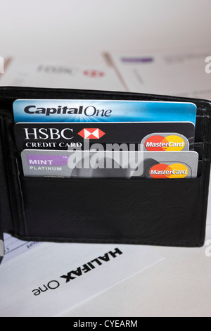 Wallet containing credit cards surrounded by credit card statements - Stock Photo