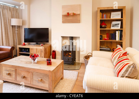 Contemporary living room with neutral colors, wood burner and wooden floor. Photographers own artwork on wall and - Stock Photo