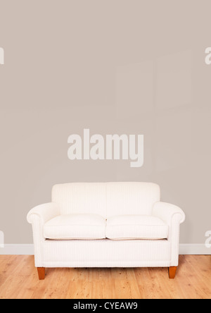 Modern cream sofa against a blank wall with lots of space for text - Stock Photo