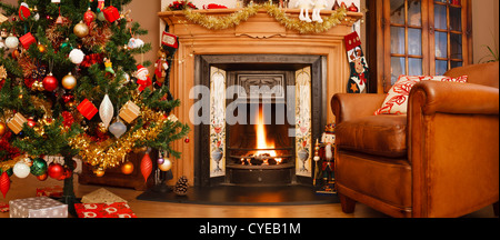 Christmas interior fire place in a living room in panoramic format - Stock Photo