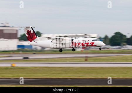 An Air Canada Jazz Dash 8 turboprop airliner. Blurred by camera panning at slow shutter speed with the landing aircraft - Stock Photo