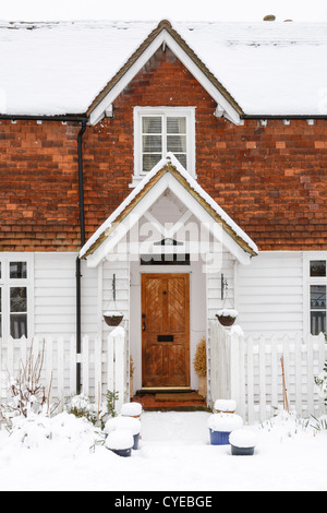 Front of clapboard home with snow on roof - Stock Photo