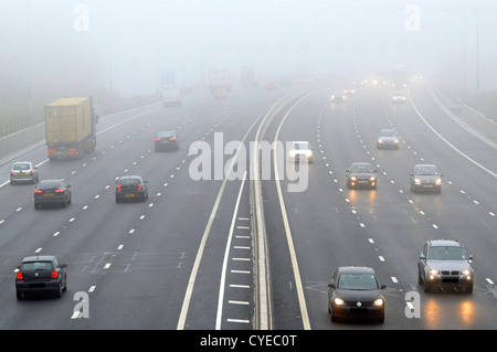 Traffic driving with headlights on in fog English M25 motorway Essex England UK - Stock Photo