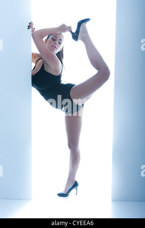 Athletic Busty Woman Posing In Doorway, ballet pose on one leg, wearing high heels and a leotard - Stock Photo