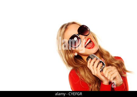 Attractive blonde woman in sunglasses singing in to microphone facing out of frame with copyspace behind. - Stock Photo