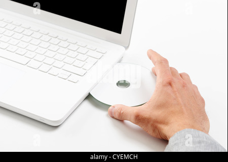 Businessman inserting a cd on white laptop - Stock Photo