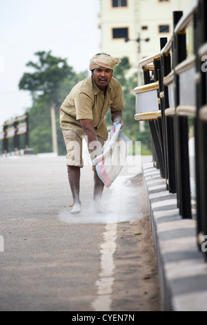 Municipal worker spreads calcium hypochlorite. Government worker spreading bleaching powder by hand on the streets - Stock Photo