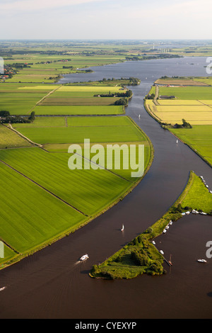 The Netherlands, near Uitwellingerga, Aerial. Farmland and boats anchored at little island. - Stock Photo