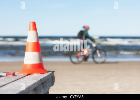 A cyclist rides along the beach on the background of the sign - Stock Photo