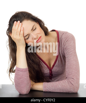 A beautiful young woman with a bad migraine leaning her head in her hands. Isolated on white. - Stock Photo