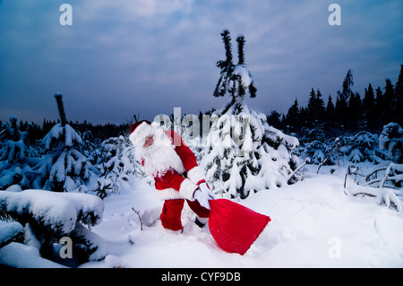 Santa Claus carrying his heavy sack with Christmas presents - Stock Photo