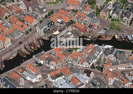 View on center of village and harbour. Shipyard for repair and construction of old fashioned fishing boats. Aerial. - Stock Photo