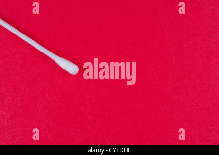 Cotton bud on red background close up - Stock Photo