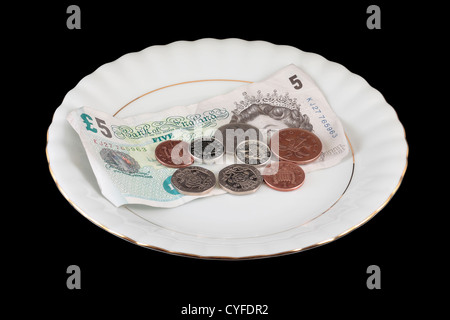 English Money on White Gold Rimmed Plate isolated on black background - Stock Photo