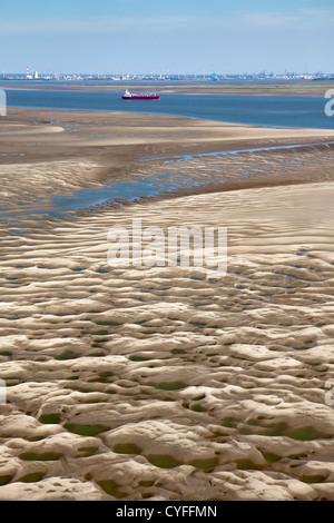 The Netherlands, Nieuw Namen, Cargo ship in Westerschelde river. Industrial area of Antwerp. Foreground tidal sandbank. - Stock Photo