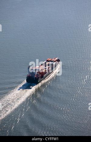The Netherlands, Nieuw Namen. Container ship in Westerschelde river. Aerial. - Stock Photo