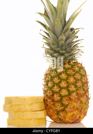 Fresh whole tropical pineapple with several slices stacked next to it on a white background - Stock Photo