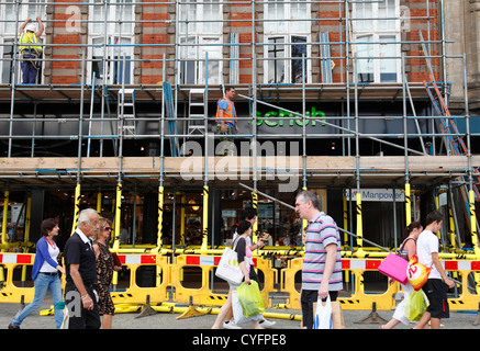 Men erecting scaffolding on a busy street in Nottingham, England, U.K. - Stock Photo