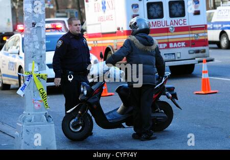 Nov. 3, 2012 - Manhattan, New York, U.S. - A police officer orders a scooter rider out of the are after cutting - Stock Photo