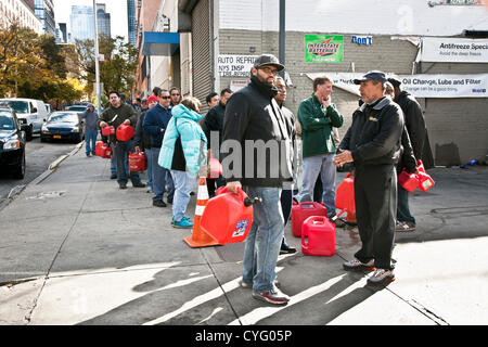 New York City, USA. 3rd November, 2012. Diverse good humored New Yorkers carrying red plastic fuel containers line - Stock Photo