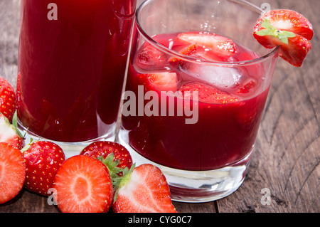Some glasses with Strawberry Liqueur on wooden background - Stock Photo