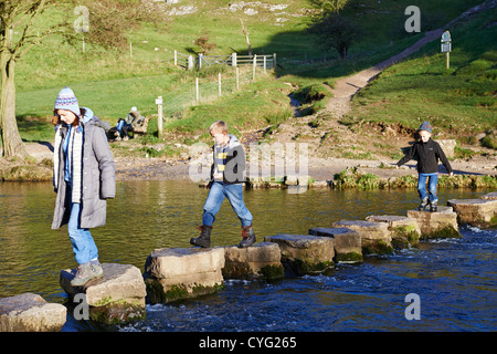 People Crossing Over The Famous Stepping Stones On The River Dove Dovedale Derbyshire UK - Stock Photo