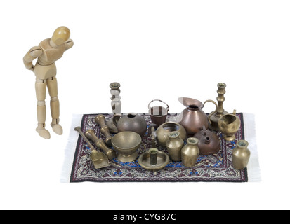 Shopping through a variety of different junk items on an intricate rug - path included - Stock Photo