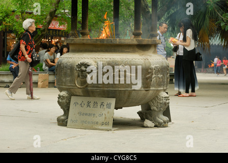 Buddhist ritual of Incense offerings placed in a censer at the entrance of Po LIn Monastery, Ngong Ping Plateau, - Stock Photo
