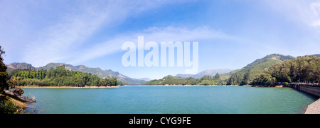 Horizontal panoramic (2 picture stitch) view of Mattupetty Dam or reservoir near Munnar in India. - Stock Photo
