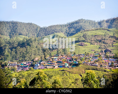 Horizontal view of the colourful lowrise houses covering the slopes of the hills in Munnar, India. - Stock Photo
