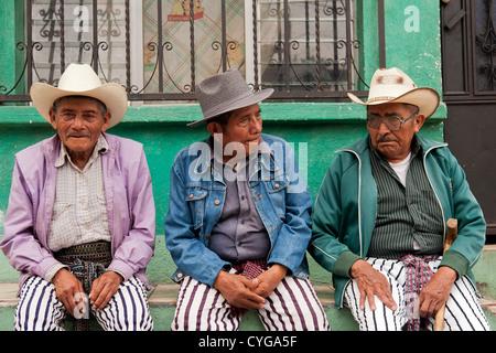 Three men await the worship of Maximón, a folk saint, and dress appropriately during Easter in Santiago Atitlan, - Stock Photo
