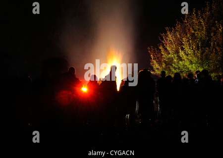 Silhouette of a crowd against a bonfire - Stock Photo